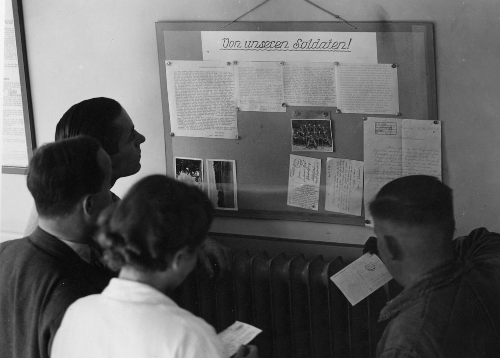 "Employees studying the board with ""letters from the front"" at the institute which displayed letters and cards written by co-workers drafted to the war."
